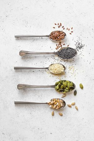 Various Seeds on white background. Assortment, set of seeds on spoons, healthy food ingredients, superfood, top view, copy space. 免版税图像