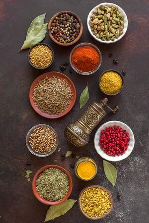 Diverses épices sur fond sombre. Assortiment, ensemble d'épices et condiments avec moulin à poivre, vue de dessus, mise à plat. Concept de cuisine de cuisine.