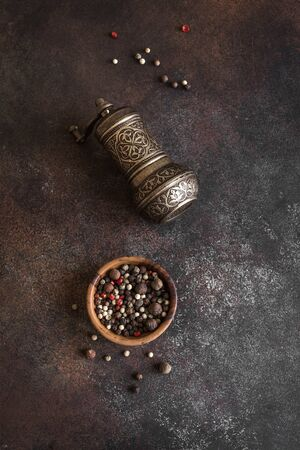 Vintage pepper mill and mixed peppercorns on dark background. Cooking and oriental spices concept, top view.