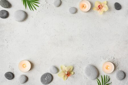Spa concept on white stone background, palm leaves, flowers, candles and zen like grey stones, top view, copy space. Standard-Bild