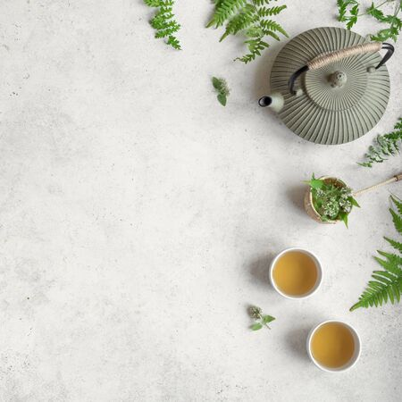 Herbal or Green Tea on white background, top view, copy space. Teapot and teacups with wild plant leaves, natural herbal tea composition. 写真素材 - 125963630
