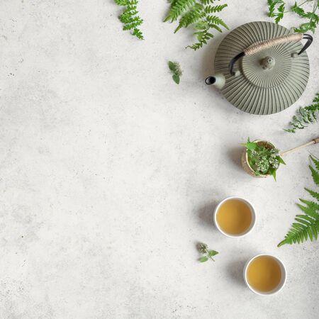 Kruiden of groene thee op witte achtergrond, bovenaanzicht, kopieer ruimte. Theepot en theekopjes met wilde plantenbladeren, natuurlijke kruidentheesamenstelling.