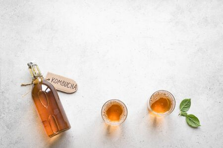 Kombucha fermented drink in glass and bottle on white background, copy space. Heathy probiotic drink - kombucha.
