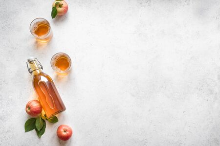 Boisson au cidre de pomme ou boisson aux fruits fermentés et pommes biologiques sur blanc, vue de dessus, espace de copie. Concept d'alimentation saine et de mode de vie. Banque d'images