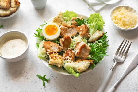 Caesar Salad on white table,close up. Homemade chicken caesar salad with grilled croutons.