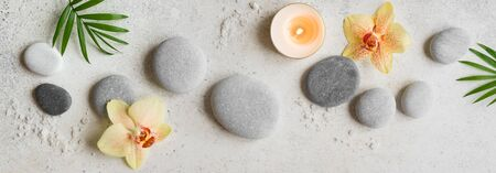 Spa concept on white stone background, tropical orchid flowers, candle and zen like grey stones, top view, banner.
