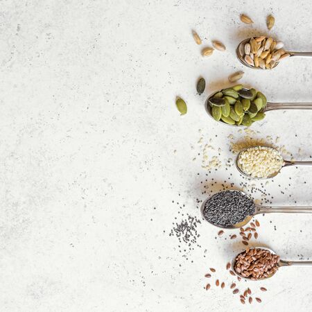 Various Seeds on white background. Assortment, set of seeds on spoons, healthy food ingredients, superfood, top view, copy space. Stock fotó