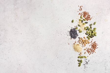 Various Seeds on white background. Assortment, set of seeds on spoons, healthy food ingredients, superfood, top view, copy space.