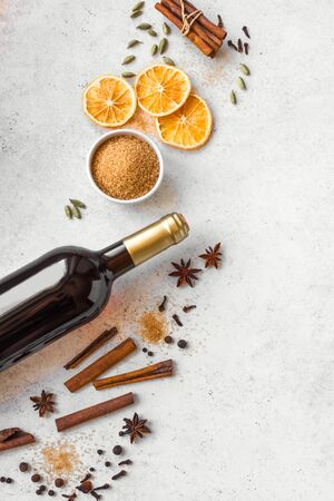 Winter Spices for Mulled Wine on white background, top view, copy space. Seasonal mulled wine ingredients - aroma spices and bottle of red wine. Stock Photo