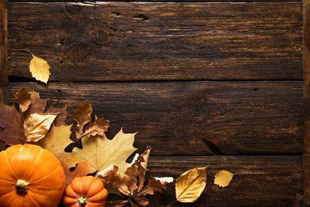 Thanksgiving oder herbstlicher Feiertagshintergrund, Draufsicht, Kopienraum. Herbstliche Feiertagskomposition mit Kürbissen, Nüssen, gelben Blättern.