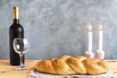 Shabbat or Shabath concept. Challah bread, shabbat wine, book and candles on table, copy space. Traditional Jewish Shabbat ritual. Reklamní fotografie