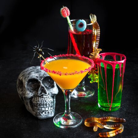 Halloween Cocktails - pumpkin spice martini, green and bloody red drinks. Festive Halloween cocktails assortment and decor for party, copy space. Reklamní fotografie