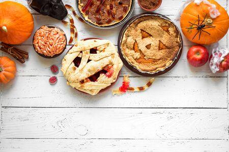 Halloween Pies - pumpkin, mummy, brain, worms. Festive Halloween homemade pastries and desserts assortment and autumn decor, top view, copy space.