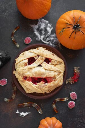 Halloween Mummy Pie, Pumpkins and Halloween Decor on dark background, top view, copy space. Homemade dessert idea for Halloween. 版權商用圖片