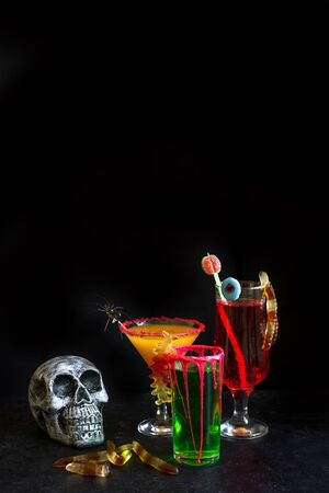 Halloween Cocktails - pumpkin spice martini, green and bloody red drinks. Festive Halloween cocktails assortment and decor for party, copy space. Stock Photo