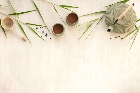 Green Tea Composition with bamboo leaves. Chinese traditional tea set, tea ceremony concept, top view, copy space. Imagens