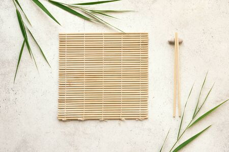 Asiatischer Lebensmittelhintergrund - Essstäbchen, Bambusmatte mit Bambusblättern auf hellem Hintergrund. Asiatisches Menüdesign, Konzept der chinesischen japanischen Küche.
