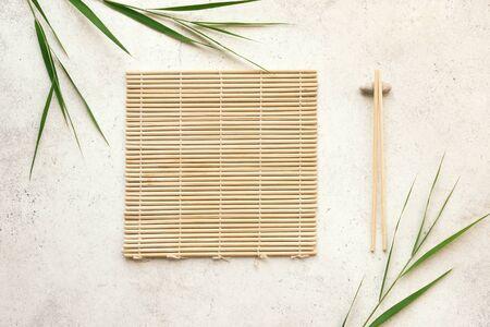 Aziatische voedselachtergrond - eetstokjes, bamboemat met bamboebladeren op lichte achtergrond. Aziatisch menuontwerp, Chinees Japans keukenconcept.