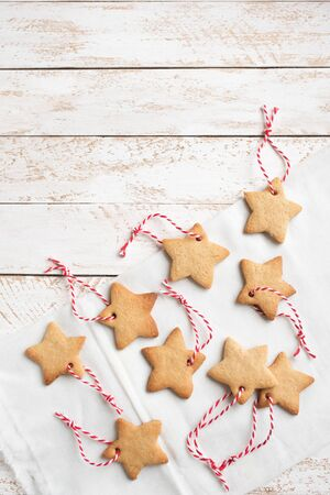 Christmas Background - Christmas star shaped gingerbread cookies with red ropes for Christmas tree decoration on white shabby background, copy space.