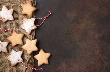 Christmas Background - Christmas star shaped gingerbread cookies with red ropes and golden balls for Christmas tree decoration on rustic background, top view, copy space. Imagens