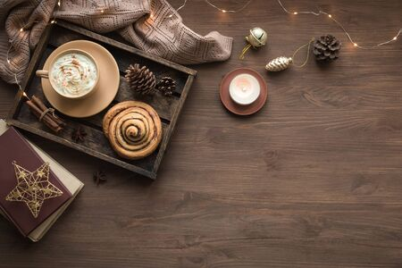 Cozy home and winter hygge concept. Seasonal winter and Christmas composition with soft plaid, garland, coffee, fresh cinnamon bun, candle, pine cones on wooden, top view, copy space.