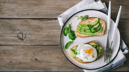 Avocado Sandwich with Poached Egg - sliced avocado and poached egg on toasted bread with arugula for healthy breakfast or snack, copy space.
