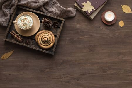 Cozy home and autumn hygge concept. Seasonal autumnal composition with soft plaid, coffee latte, fresh pastry cinnamon bun, candle on wooden, top view, copy space. Imagens