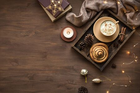 Cozy home and winter hygge concept. Seasonal winter and Christmas composition with soft plaid, garland, coffee, cinnamon bun, candle, pine cones on wooden, top view, copy space.