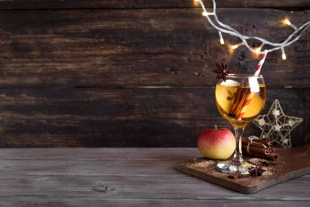 Hard apple cider (sangria, punch, fruit wine) for autumn and winter holidays - homemade festive Christmas, Thanksgiving drink on wooden table, copy space.