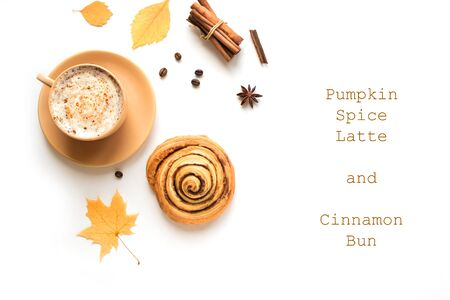Pumpkin Spice Latte and Cinnamon Bun for breakfast or break isolated on white background. Cup of coffee and homemade bun with seasonal autumnal leaves, copy space.