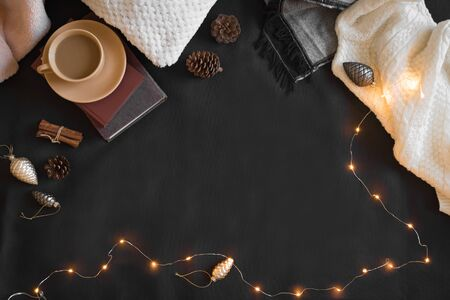 Christmas coziness concept. Seasonal winter composition with soft plaid, coffee and book. Cozy home and hygge concept, copy space. 写真素材