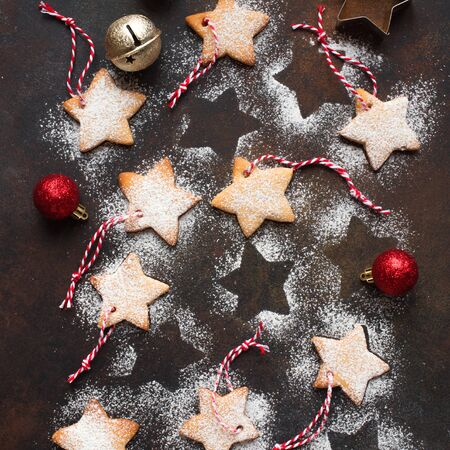 Christmas Background - Christmas star shaped gingerbread cookies with red ropes and golden balls for Christmas tree decoration on rustic background, top view. Imagens