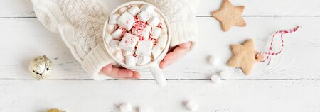 Christmas Hot chocolate with marshmallows, peppermint candies in hands on white table, top view, banner. Hot cocoa drink for Christmas and winter holidays with festive decor.