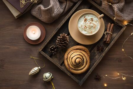 Cozy home and winter hygge concept. Seasonal winter and Christmas composition with soft plaid, garland, coffee, cinnamon bun, candle, pine cones on wooden, top view, copy space. 写真素材