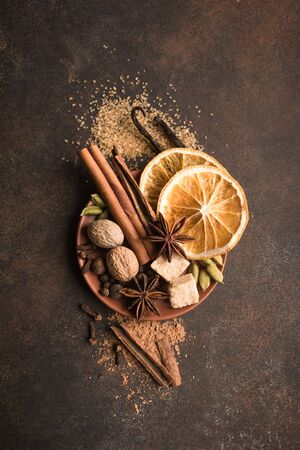 Winter Spices and Brown Sugar on dark rustic background, top view, copy space. Mulled wine or Christmas seasonal baking ingredients - aroma spices.