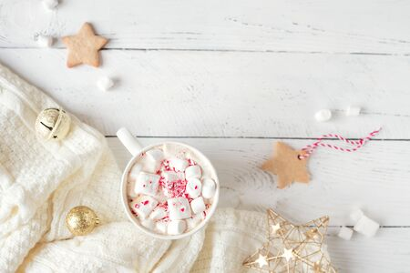 Christmas Background - Hot chocolate with marshmallows, peppermint candies in white mug, top view, copy space. Hot cocoa drink for Christmas and winter holidays with warm scarf festive decor.