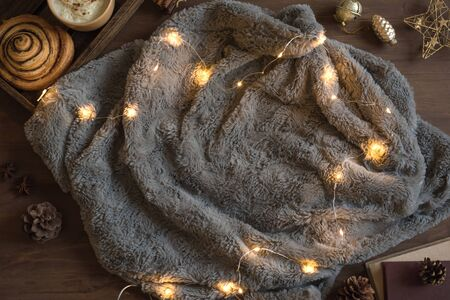 Cozy home and winter hygge concept. Seasonal winter and Christmas composition with grey soft plaid, garland, coffee, fresh cinnamon bun, pine cones on wooden, top view, copy space.
