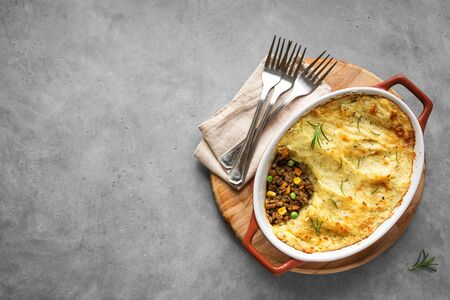 Shepherd's Pie with ground beef, potato and cheese on grey background, top view, copy space. Traditional homemade casserole - Shepherds Pie. Stock Photo