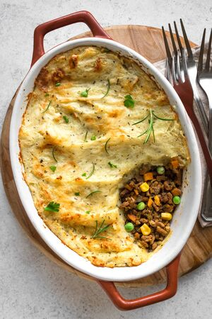 Shepherds Pie with ground beef, potato and cheese on white background, top view, copy space. Traditional homemade casserole - Shepherds Pie. Stock Photo