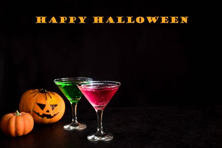 Halloween Cocktails - green and bloody red martini drink. Festive Halloween cocktail with pumpkin and halloween decor for party, copy space.