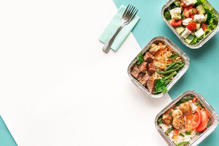 Consegna di cibo sano. Porta via il pasto giornaliero biologico su blu, copia spazio. Concetto di cibo pulito, cibo sano, nutrizione fitness da asporto in scatole di alluminio, vista dall'alto.