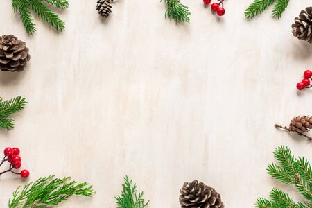 Christmas composition. Christmas decor, pine cones, fir branches on white wooden background. Flat lay, top view, copy space. Stock Photo