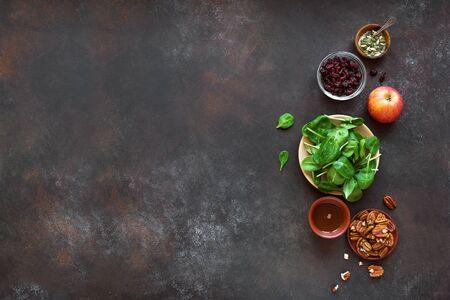 健康的な季節のビーガンサラダを調理するための健康的な秋サラダ成分 - 赤ちゃんほうれん草の葉、リンゴ、ピーカンナッツ、ドライクランベリー、素朴な背景に蜂蜜、コピースペース。
