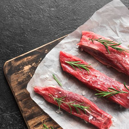 New York Strip Steak with salt and rosemary on black background, top view, copy space. Uncooked raw beef strip steaks.