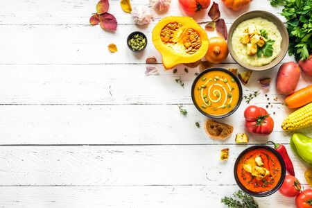 Autumn soups. Set of various seasonal vegetable soups and organic ingredients on white background, top view, copy space. Homemade colourful vegan soups.