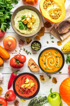 Autumn soups. Set of various seasonal vegetable cream soups and organic ingredients on white background, top view. Homemade colourful soups.