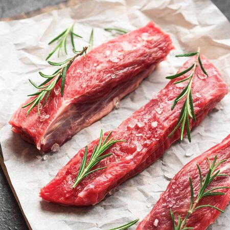 New York Strip Steak with salt and rosemary on black background, top view, close up. Uncooked raw beef strip steaks.