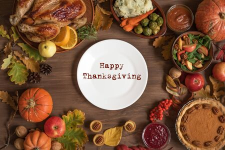 Thanksgiving dinner background with turkey and all sides dishes, pumpkin pie, fall leaves and seasonal autumnal decor around white plate, top view, copy space.