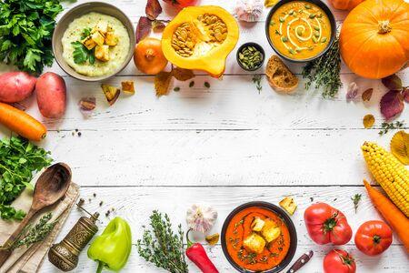 Herbstsuppen. Satz verschiedene saisonale Gemüsesuppen und organische Zutaten auf weißem Hintergrund, Draufsicht, Kopienraum. Hausgemachte bunte vegane Suppen.