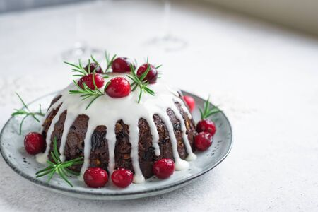 Christmas Pudding, Fruit Cake decorated with icing and cranberries on white, copy space. Homemade traditional Christmas festive dessert - Christmas Pudding. 版權商用圖片